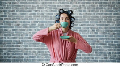 Portrait of lady with hair curlers drinking tea then smiling...