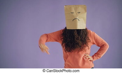Portrait of lady with paper bag on head showing thumbs-down...