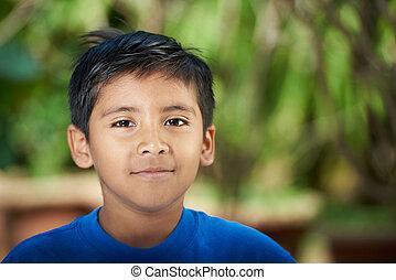 Portrait of latino boy on blurred sunny background
