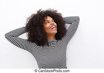 laughing african american woman with hands in curly hair