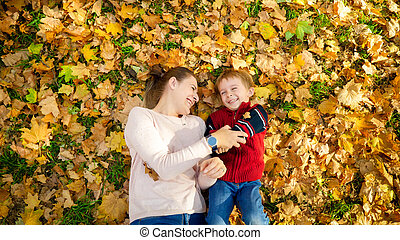 Portrait of laughing and smiling boy with young mother lying on leaves at autumn park
