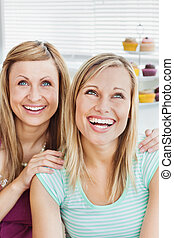 Portrait of laughing friends sitting in the kitchen