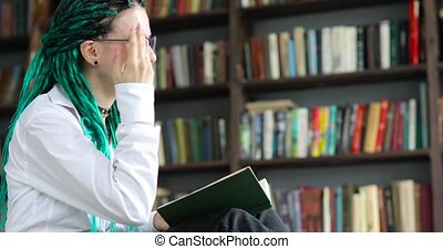 Portrait of laughing girl student with dreads hairs in glasses reads book in library sitting on floor, side view. Girl with green dreadlocks learns literature at University campus. Studying concept.