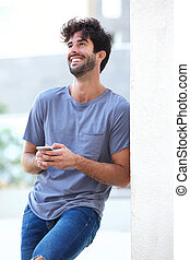 Portrait of laughing man holding phone leaning on wall outside