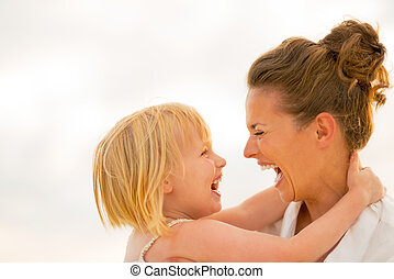 Portrait of laughing mother and baby girl hugging on beach at the evening