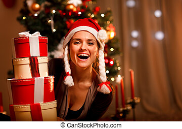 Portrait of laughing woman near Christmas tree looking out...