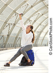 laughing woman sitting on suitcase taking selfie
