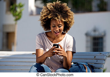 african american female sitting outdoors reading text message on smart phone