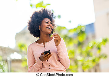 laughing young african american woman with cellphone outside in city