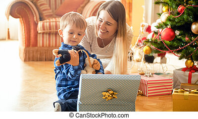 Portrait of laughing young mother with little smiling boy opening Christmas gifts