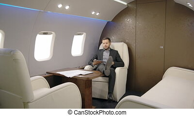 Portrait of lawyer succesful man taking a seat in his private plane and reading news on his tablet. entrepreneur airplane