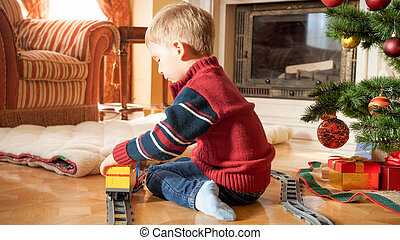 Portrait of little 3 years old boy sitting next to Christmas tree and playing with toy railroad. Child receiving presents and toys on New Year or Xmas