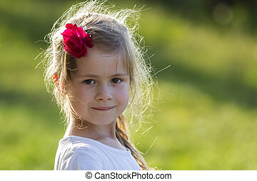 Portrait of little adorable blond girl with gray eyes and red rose in beautiful long hair smiling in camera on bright blurred green outdoors background. Beauty and innocence of childhood concept.