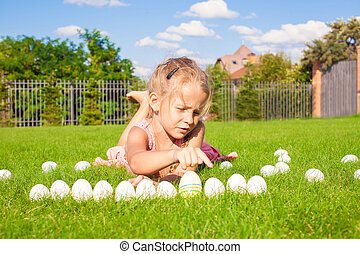 Portrait of little adorable girl playing with white Easter eggs on green grass