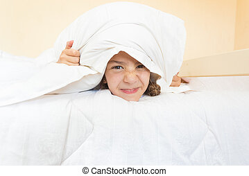 portrait of little angry girl lying in bed with pillow on head
