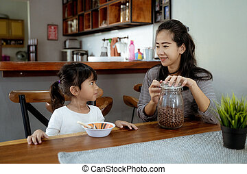 Little asian girl eating cereal for breakfast with mom