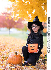 Portrait of little asian girl in witch costume