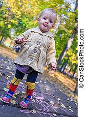 Portrait of Little beautiful girl walking alone in autumn park