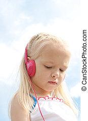 Portrait of little blonde girl in headphones