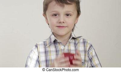 Portrait of little boy biting apple at home