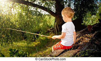 Portrait of little boy fishing with old wooden rod on the ...