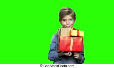 Portrait of little boy in denim jacket with gift boxes.