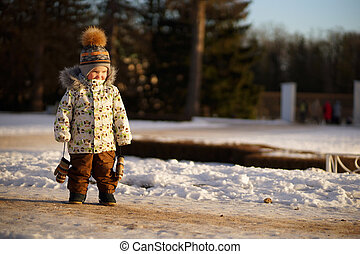 Portrait of little boy in winter clothes, hat with pompom and mittens on strings standing on snow in sunny winter park