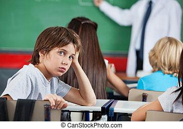 Portrait Of Little Boy Leaning At Desk - Side view portrait...