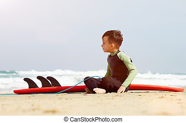 portrait of little boy learn to surf at sea