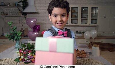 Portrait of little boy offering gift box on camera