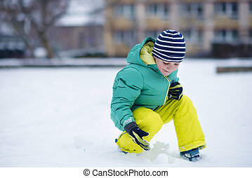 Portrait of little boy playing with snow in winter