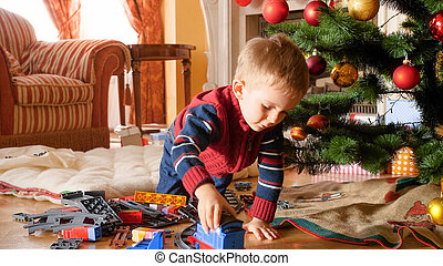 Portrait of little boy playing with toy train and railways on floor under Christmas tree
