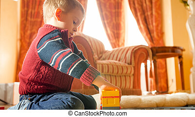Portrait of little boy playing with toys on wooden floor at living room against big window