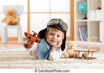 portrait of little boy playing with wooden airplane