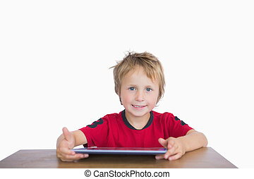 Portrait of little boy sitting at desk with digital tablet...