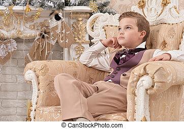little boy sitting on chair on Christmas