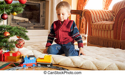 Portrait of little boy sitting on floor and playing with toy railroad that Santa gave him for Christmas. Child receiving presents and toys on New Year or Xmas