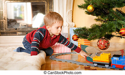 Portrait of little boy sitting on floor at living room and looking at toy train on railways under Christmas tree
