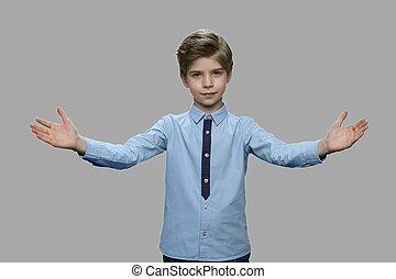 Portrait of little boy spreading hands on gray background.