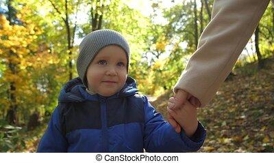 Portrait of little boy walking with mom in park