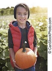 Portrait of little boy with pumpkin