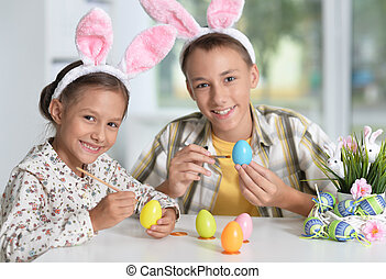 brother and sister painting traditional Easter eggs