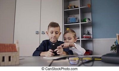 Portrait of little brothers who are using smartphone for chatting with friend sitting at the desk at home