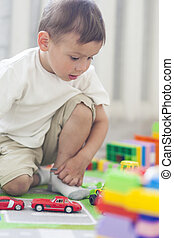 Portrait of Little Caucasian Boy Playing with Toys Indoors