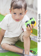 Portrait of Little Caucasian Boy Playing with Toys