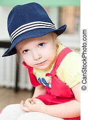Portrait of little Caucasian girl in blue hat