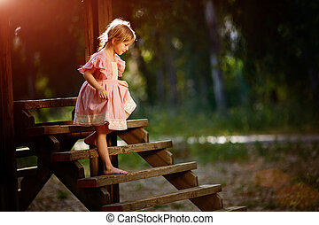 Portrait of little Caucasian girl wearing pink dress standing on wooden bridge, covering face and crying in forest