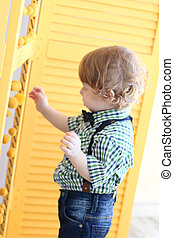 Portrait of little cute boy with curly hair touching screen with yellow balls