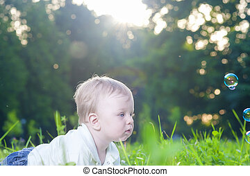 Portrait of Little Cute Caucasian Boy Playing With Soap Bubbles Outdoors
