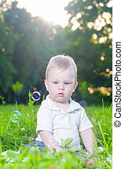Portrait of Little Cute Caucasian Boy Sitting Alone on Grass Outdoors.